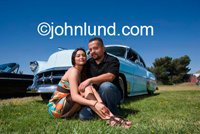 Happy Hispanic couple sitting on the green grass in front of their classic vintage show car -  a low rider car - in Northern California.